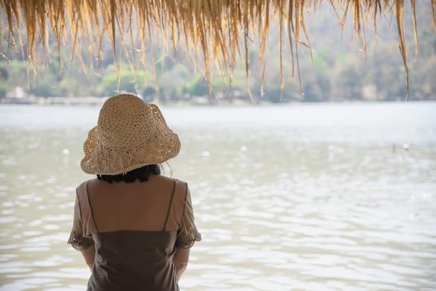 Dame heureuse pendant les vacances à la nature du site de l'eau