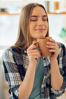 Dame heureuse tenant une tasse près de son visage et fermant les yeux tout en sentant la boisson