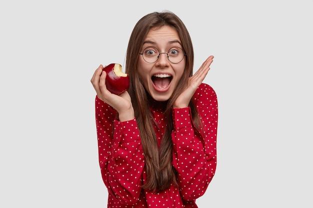 Dame heureuse trop émotive lève les mains près du visage, ouvre largement la bouche, mange une pomme savoureuse, porte des lunettes transparentes