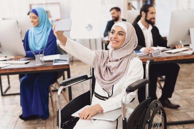 Dame en hijab fait un appel vidéo sur le téléphone au bureau.