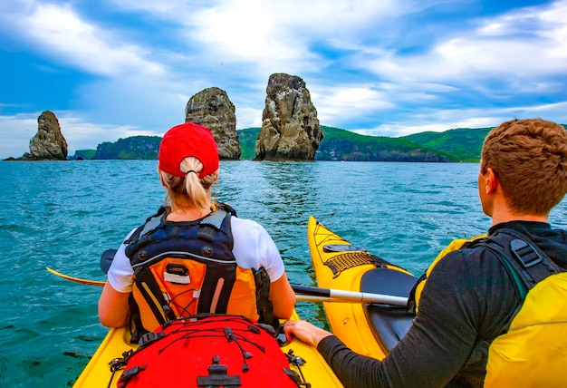 Dame et hommes pagayant le kayak dans la baie d'avacha
