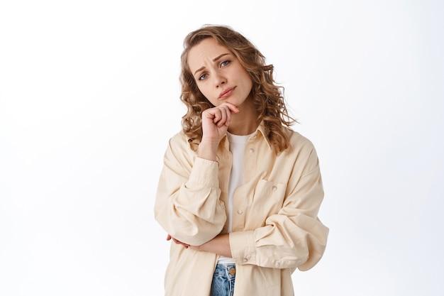 Dame indécise regardant l'avant réfléchie, prenant une décision, fronçant les sourcils et regardant pensivement, debout dans des vêtements modernes contre un mur blanc