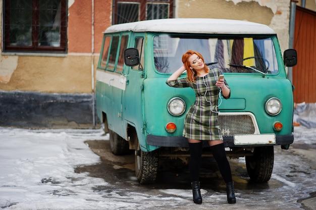 Dame jeune femme aux cheveux rouges avec téléphone portable et des écouteurs, vêtue d'une robe dans le vieux bus monospace vintage.