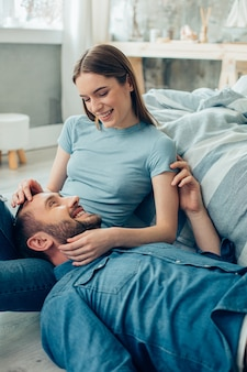 Dame joyeuse assise et souriante gentiment à un petit ami positif allongé sur ses genoux