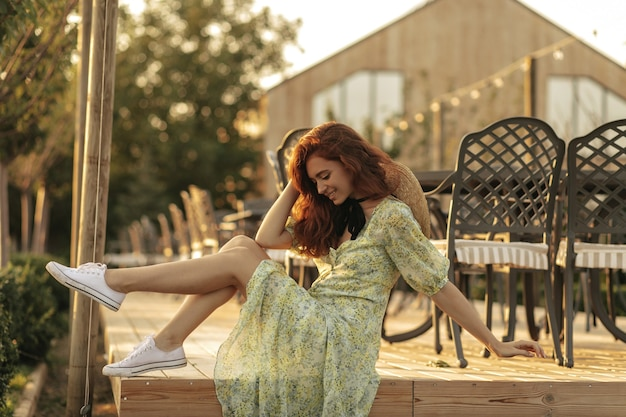 Dame joyeuse avec une coiffure ondulée rouge, un chapeau de paille et un bandage noir sur le cou en robe verte imprimée et des baskets légères souriant sur le mur du café