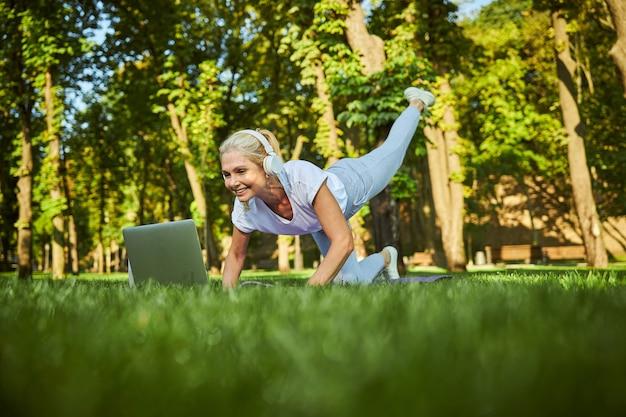 Dame joyeuse dans les écouteurs faisant de l'exercice et souriant tout en regardant une formation en ligne sur un ordinateur portable à l'extérieur
