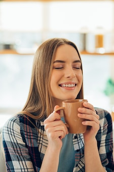 Dame joyeuse fermant les yeux et souriant tout en tenant une tasse de thé