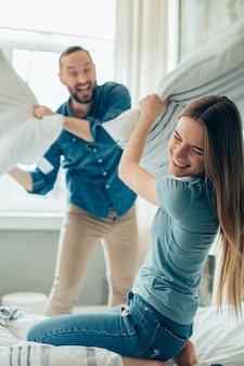 Dame joyeuse profitant d'une drôle de bataille d'oreillers avec un petit ami pendant la quarantaine