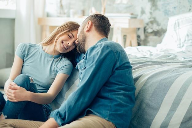 Dame joyeuse se penchant vers son homme bien-aimé et fermant les yeux en souriant