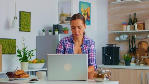 Dame joyeuse sirotant du thé vert et publiant sur un ordinateur portable pendant le petit-déjeuner dans une cuisine confortable. travailler à domicile à l'aide d'un appareil doté de la technologie internet, naviguer, rechercher un gadget le matin.