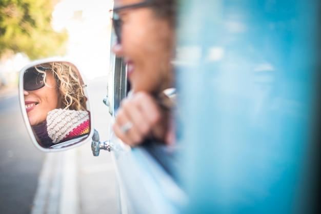 Une dame joyeuse sourit et voyage sur un vieux véhicule bleu et se regarde dans le rétroviseur
