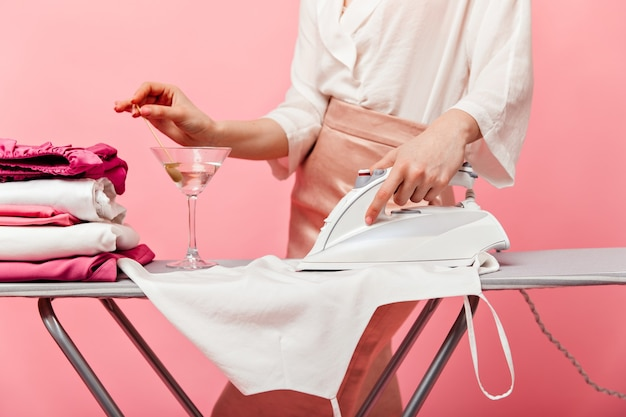 Dame en jupe de soie et chemisier blanc repasse ses vêtements et sort l'olive du verre à martini