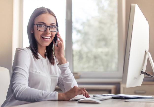 Dame à lunettes parle au téléphone.