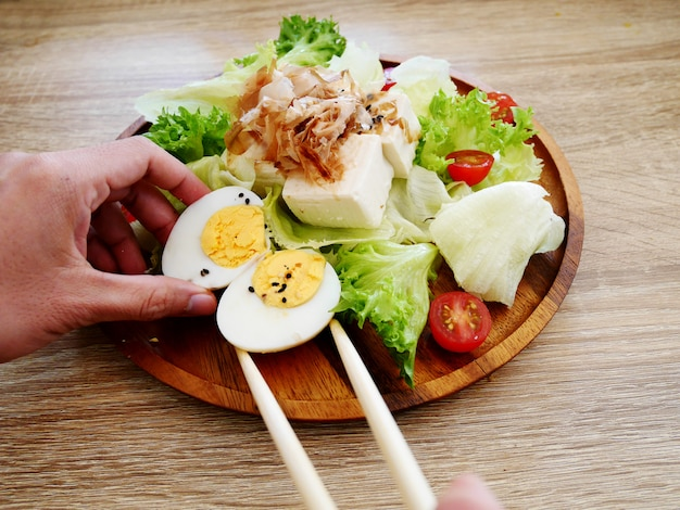 Dame main prépare la salade de tofu japonais avec oeuf à la coque avec des baguettes dans la plaque de bois