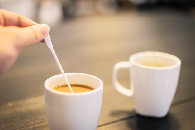 Dame main tenant une cuillère à café et en remuant le café chaud