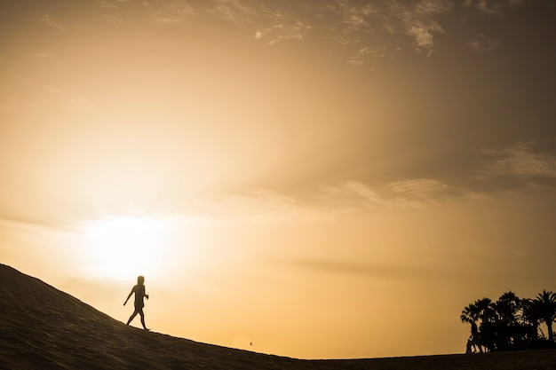 Dame marchant sur un désert de dunes aux îles canaries lors d'un magnifique coucher de soleil magnifique et doré aux couleurs orange et jaune.