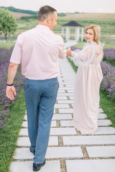 Dame mature blonde en robe élégante, tenant la main et marchant avec son bel homme à l'extérieur