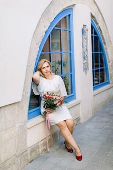 Dame mature élégante en robe élégante blanche se présentant à la caméra avec un bouquet de fleurs à l'extérieur de la ville. fenêtre vintage bleue dans la ville antique sur fond.