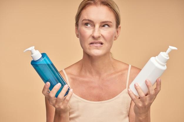 Dame mature tenant deux bouteilles de crème isolé sur fond beige