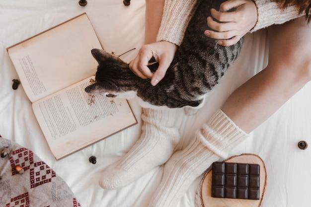 Dame méconnaissable caressant chat près de livre et de chocolat