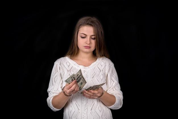 Dame menottée comptant de l'argent, isolée sur fond noir