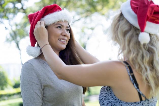 Dame, mettre, bonnet noël, sur, sourire, tête amie, dans parc