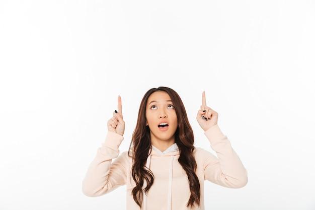 Dame mignonne asiatique pointant.