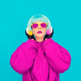 Dame de mode glamour dans des vêtements lumineux, écouter de la musique. toutes les nuances de musique