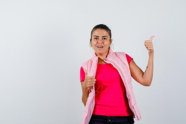 Dame montrant double pouce levé en t-shirt, gilet et à la joyeuse