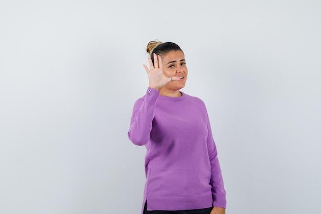 Dame montrant un geste d'arrêt en blouse de laine et ayant l'air confiant