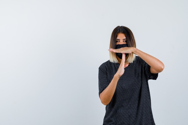 Dame montrant le geste de pause en robe noire, masque médical et à la recherche résolue. vue de face.