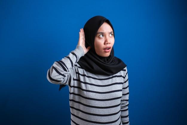 Dame musulmane en écoutant attentivement, la main sur l'oreille sur fond bleu