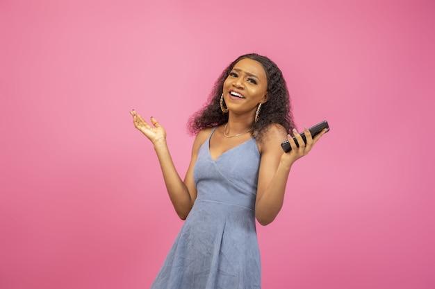 Une dame noire excitée tenant son téléphone hausse la main.