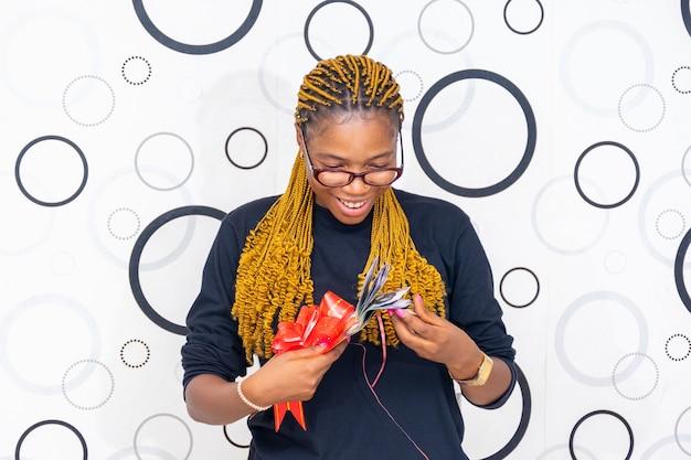 Une dame noire heureuse d'ouvrir une enveloppe lui a offert de trouver de l'argent dedans.