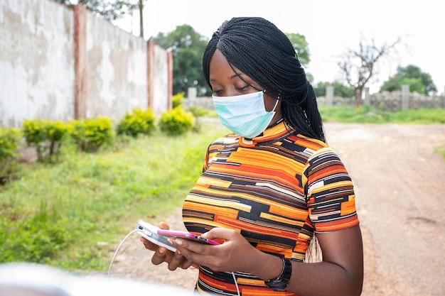 Dame noire utilisant une banque d'alimentation pour charger son téléphone en plein air