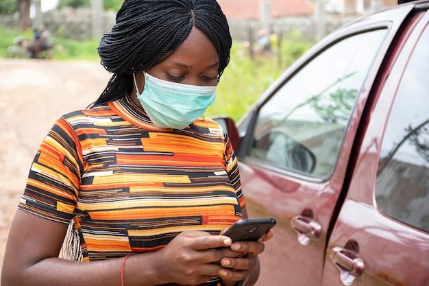 Dame noire utilisant son téléphone à l'extérieur, portant un masque facial