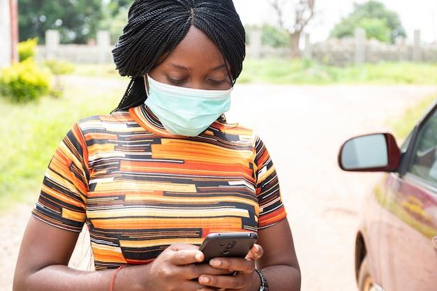 Dame noire utilisant son téléphone en plein air