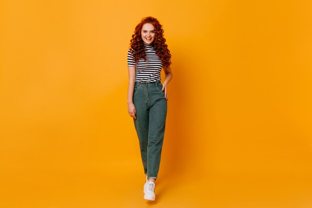 Dame en pantalon en jean élégant et haut rayé posant sur l'espace orange. plan complet d'une fille rousse.