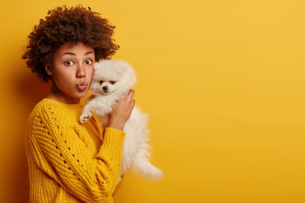 Dame à la peau foncée garde les lèvres arrondies, veut embrasser un animal adorable, joue avec un petit chiot