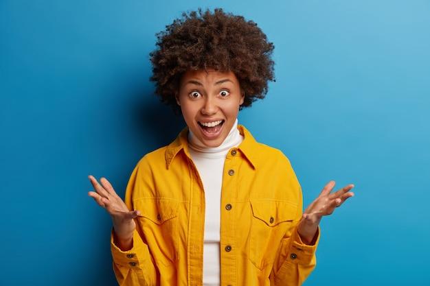 Une dame à la peau sombre surprise crie d'excitation, lève les paumes, réagit émotionnellement aux grosses ventes en magasin, n'en croit pas ses yeux, porte une chemise jaune, pose sur fond bleu