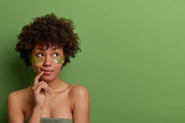La dame pensive prend soin de la peau et du corps, s'applique sous les patchs oculaires après la douche, garde le doigt près des lèvres, reçoit un traitement de rajeunissement, une procédure de cosmétologie anti-âge, se tient à l'intérieur
