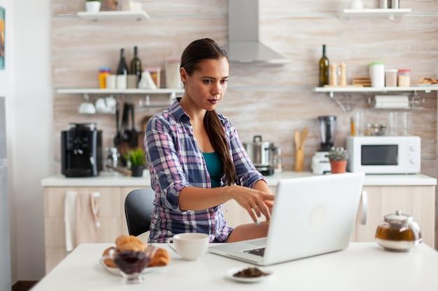 Dame pointant sur l'écran de l'ordinateur portable pendant la matinée dans la cuisine avec petit-déjeuner à côté d'elle et tasse de thé vert