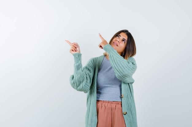 Dame pointant vers le coin supérieur gauche dans des vêtements décontractés et à la recherche d'espoir, vue de face.