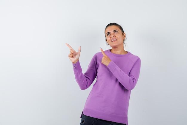 Dame pointant vers le haut dans un chemisier en laine et regardant joyeux