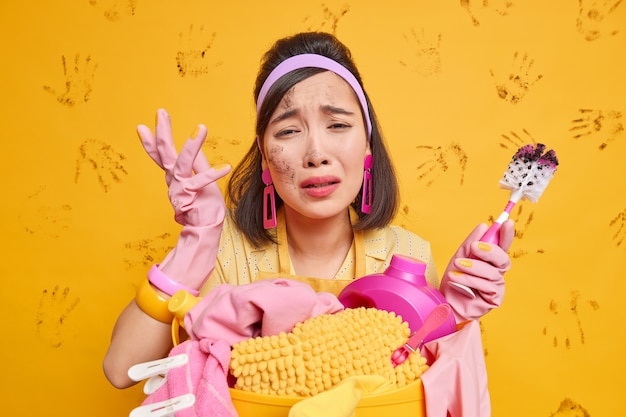 Dame porte des gants de protection en caoutchouc bandeau tablier tient une brosse de toilette sale se tient près d'un panier à linge avec des pinces à linge et du détergent isolé sur jaune