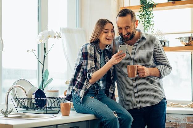 Dame positive assise dans la cuisine et montrant quelque chose de drôle dans un smartphone à son petit ami