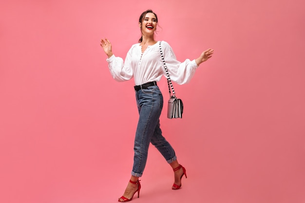 Dame positive en tenue élégante pose avec sac à main. femme souriante avec rouge à lèvres et sac rayé se déplace sur fond isolé. .