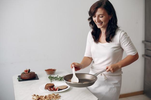 Dame prépare le dessert. confiseur cuit des crêpes. femme tient une poêle à frire dans ses mains.