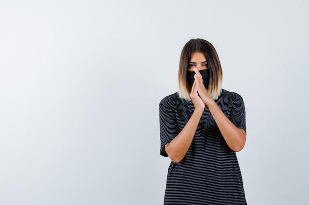 Dame pressant les mains ensemble tout en priant en robe noire, masque médical et à la recherche d'espoir. vue de face.