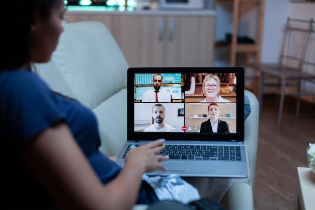 Dame en pyjama assise sur un canapé ayant une réunion en ligne avec les partenaires du projet
